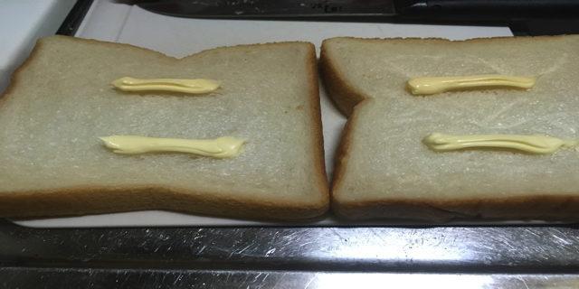 パンにバターを塗っている写真